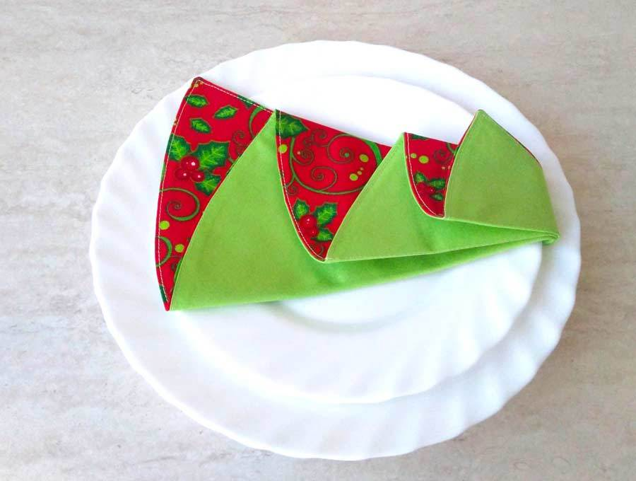 christmas tree napkins tucked between plates