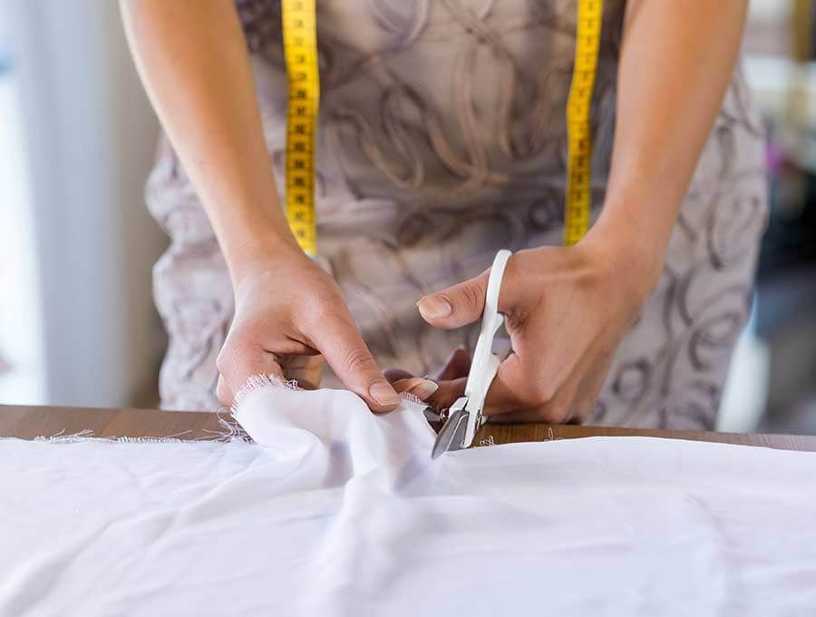 size of yard of fabric - woman cutting fabric sold by the running yard