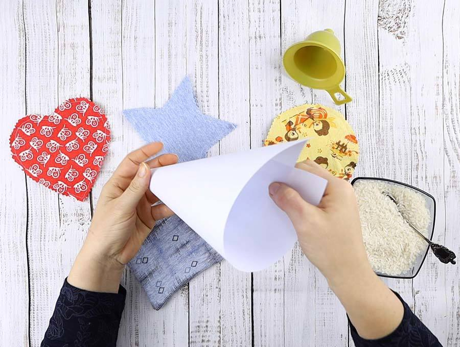 using a paper funnel to fill up a diy hand warmer with rice