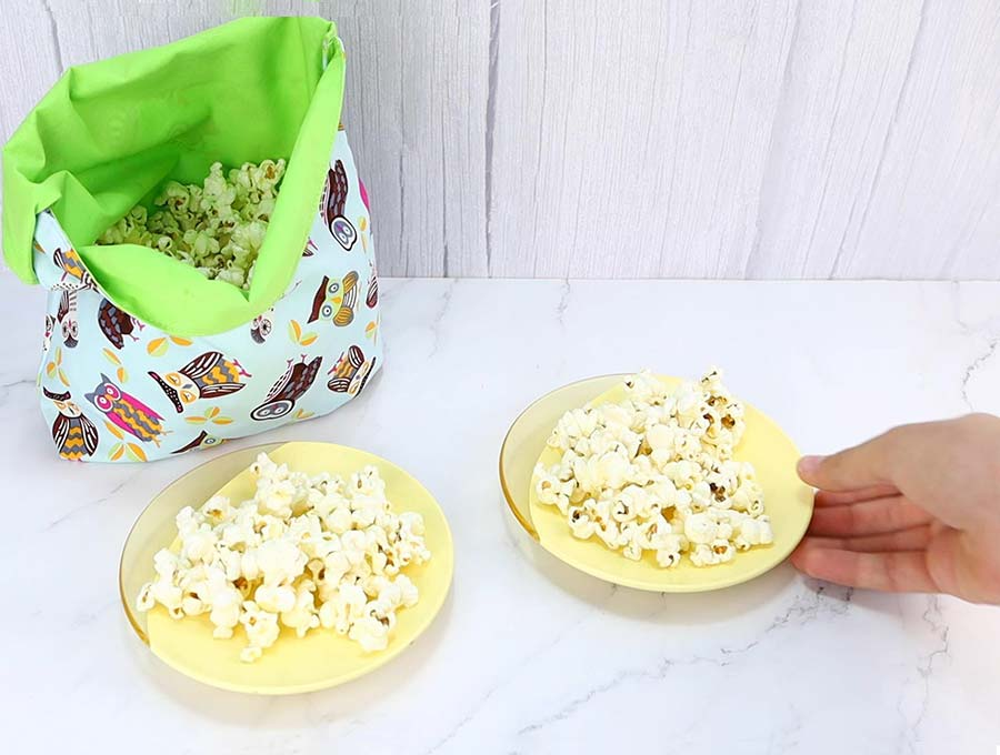 microwave popcorn bag with 2 plates full of popcorn