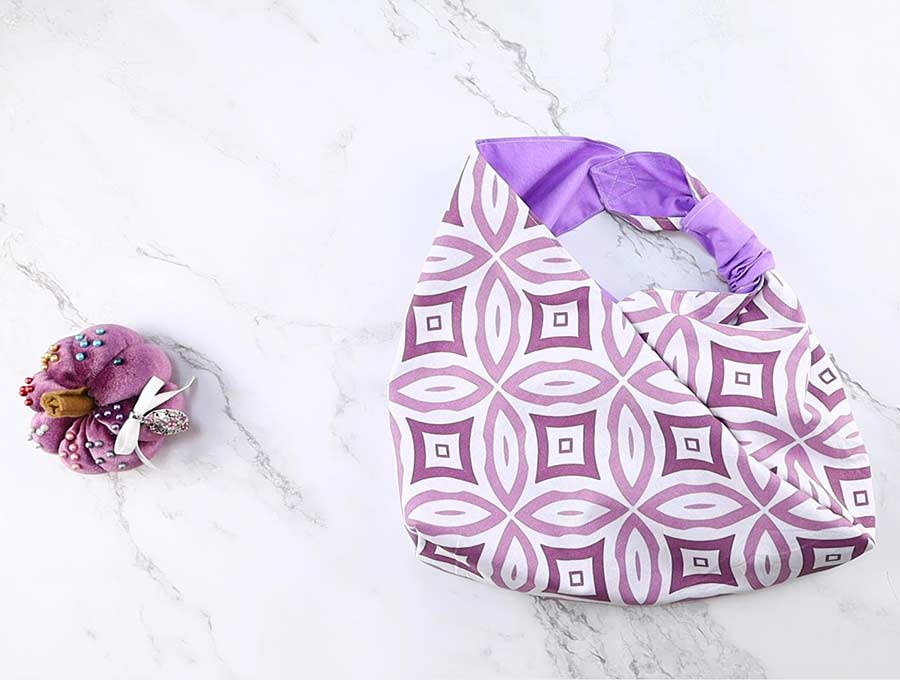 overlapping the handles of the origami bag