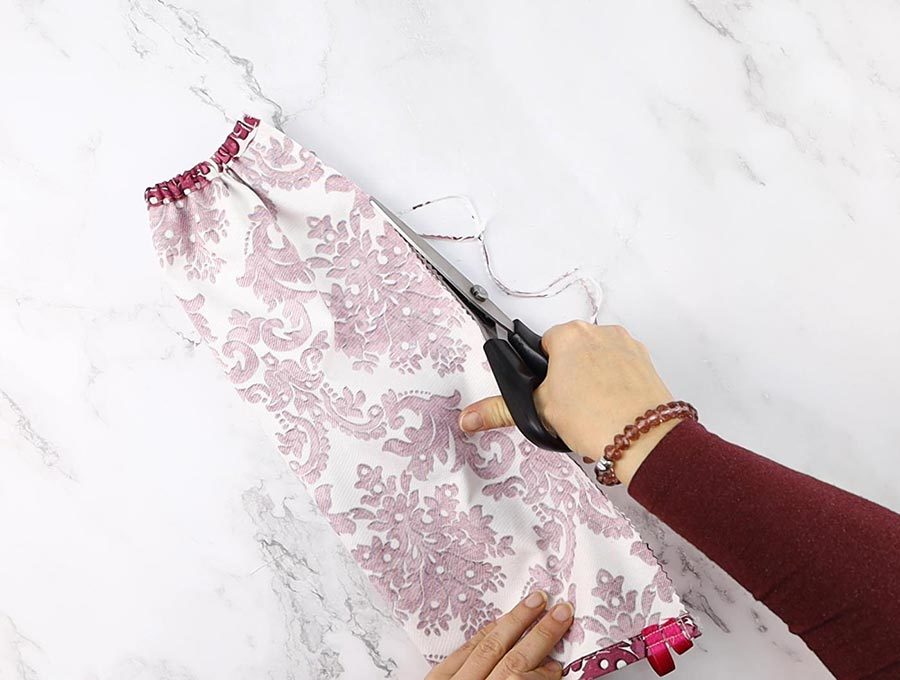 finishing the edges of the plastic bag holder with pinking shears