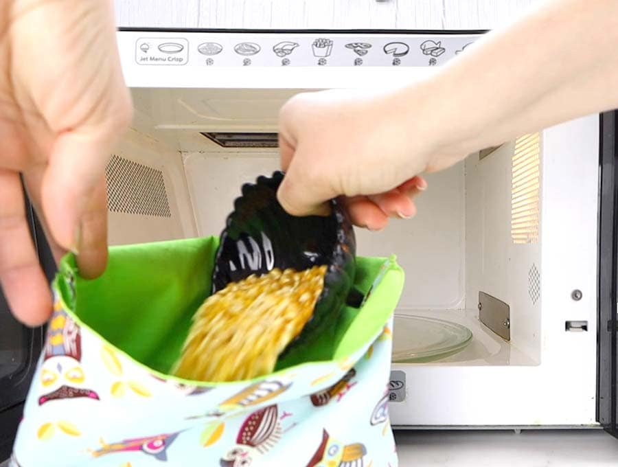 pouring kernels in a diy reusable popcorn bag in front of a microwave