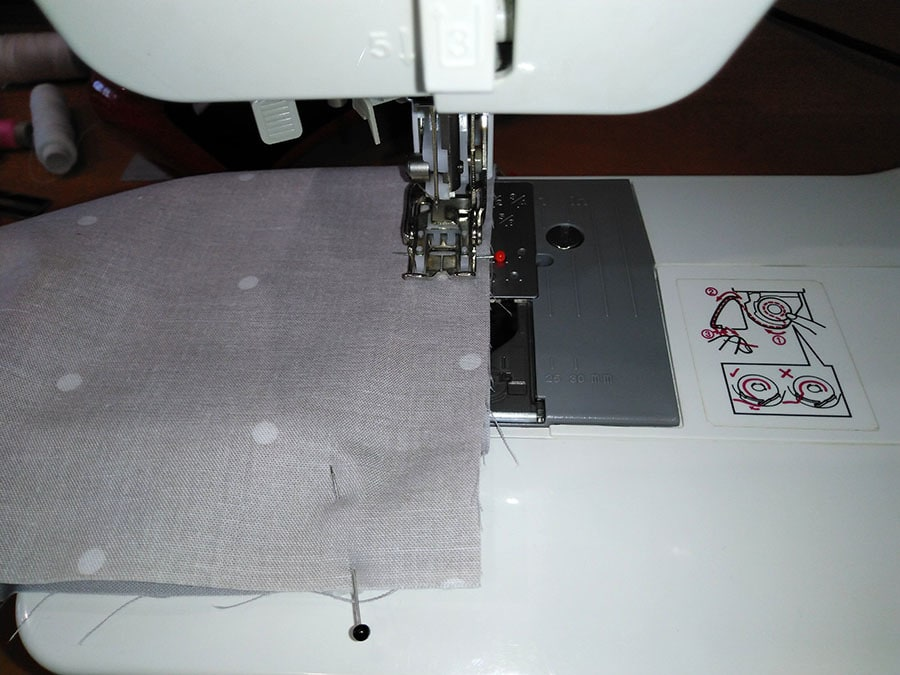 sewing through the layers of the surgical facemask with a sewing machine