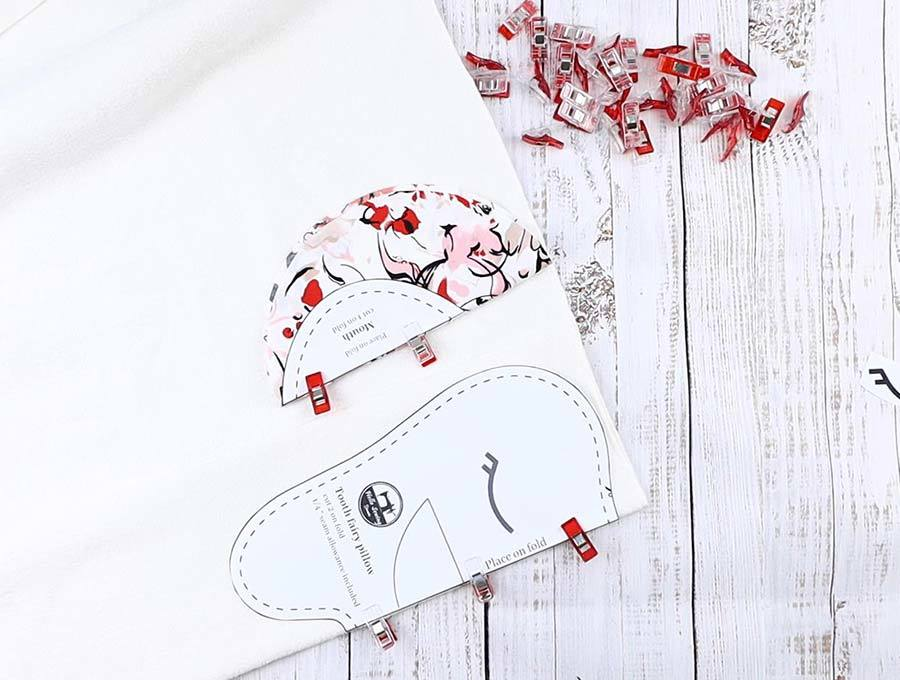 cutting out fabrics according tot he tooth fairy pillow patterns
