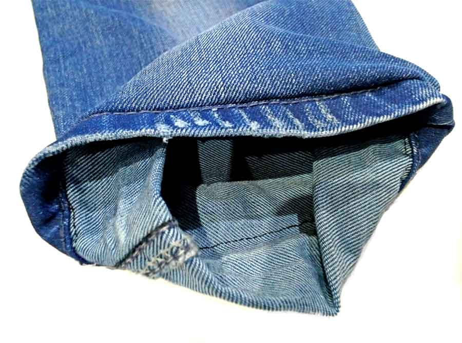unfolding the hem to trim the exess